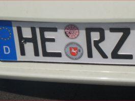 Autokennzeichen aus Helmstedt an einem weißen Auto am Bahnhof Wolfsburg.