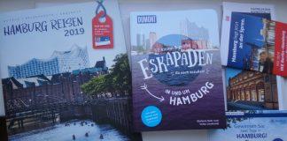 Hamburg-Reise-Broschüren, in der Mitte das Buch 52 kleine und große Eskapaden in und um Hamburg, Ab nach draußen